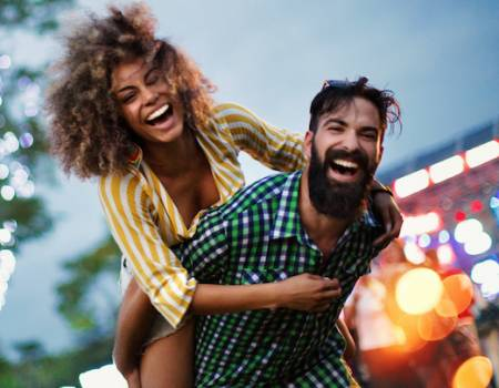 woman on mans back having fun at music festival