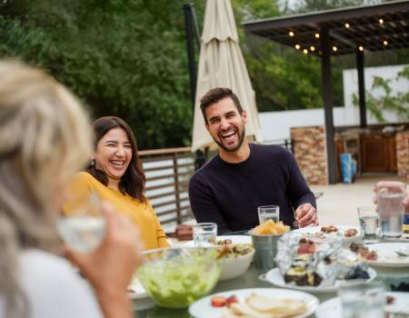 two friends sitting at a table at a restaurant laughing with table full of food