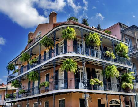 new orleans french quarter building with ferns on a balcony