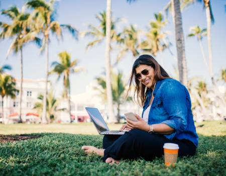 young woman with laptop, phone and coffee sits in park with palm trees in the background