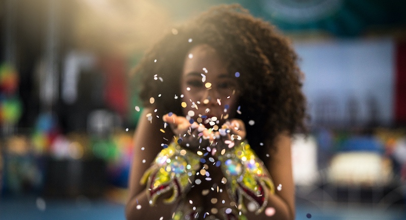 woman blowing confetti into air at mardi gras new orleans